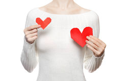 Girl hold and compare two origami hearts Stock Image