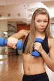 Girl hold dumbbells in hand with strong abdomen Royalty Free Stock Image