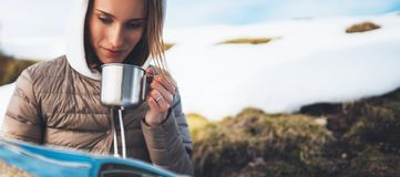 Girl hold in hands cup of drinks, relax tourist look on map, people planning trip in snow mountain, hipster enjoy on background. Winter nature, journey royalty free stock photos