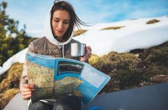 Girl hold in hands cup of drinks, relax tourist look on map, people planning trip in snow mountain, hipster enjoy on background stock photo