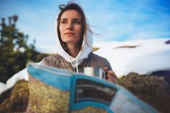 Girl hold in hands cup of drinks, relax tourist look on map, people planning trip in snow mountain, hipster enjoy on background. Winter nature, journey stock images