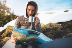 Girl hold in hands cup of drinks, relax tourist look on map, people planning trip in snow mountain, hipster enjoy on background w royalty free stock image