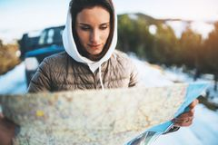 Girl hold in hands looking on map, people planning trip in snow mountain, relax tourist travels by auto car, hipster enjoy winter. Nature, journey landscape stock image