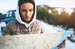 Girl hold in hands looking on map, relax tourist travels by auto car, people planning trip in snow mountain, hipster enjoy winter stock photos