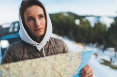 Girl hold in hands looking on map, relax tourist travels by auto car, people planning trip in snow mountain, hipster enjoy winter royalty free stock photos