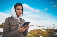 Girl hold in hands mobile phone, person type message on smartphone in landscape trip, tourist travels planning trip in snow mount. Ain on blue sky background royalty free stock photography