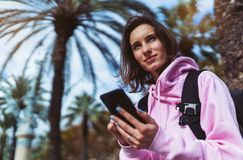 Girl hold in hands mobile phone, person type message on smartphone, relax tourist travels planning trip in sun city, hipster enjoy. Journey in cityscape royalty free stock images