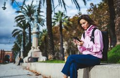 Girl hold in hands mobile phone, person type message on smartphone, relax tourist travels planning trip in sun city, hipster enjoy. Journey in cityscape stock photography