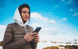 Girl hold in hands mobile phone, tourist planning trip in snow mountain on blue sky background, person type message on smartphone. In landscape trip, enjoy royalty free stock photos