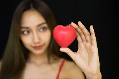Girl hold red heart toy. Beautiful Asian woman hold red heart toy on hand with black background with copy space for text. Health care or valentine love concept Stock Image