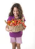 Girl holdin a basket of tomatoes Stock Images