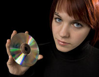 Girl holdind a compact disc. Girl holding a compact disc and amicably smiling Stock Photos