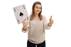 Girl holding ace of spades card and giving thumb up. Joyful girl holding an ace of spades card and giving a thumb up isolated on white background Royalty Free Stock Image