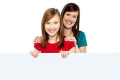 Girl holding ad board with her mother behind her Royalty Free Stock Photography