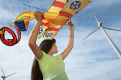 Girl Holding Airplane Kite At Wind Farm Stock Image
