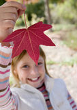 Girl (7-9) holding aloft red maple leaf in park in autumn, smiling, close-up, portrait Royalty Free Stock Images