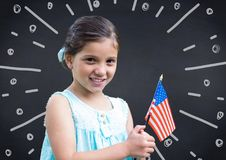 Girl holding american flag against navy chalkboard and white fireworks doodle Stock Images
