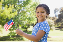 Girl holding the American flag at park Stock Photos