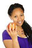 Girl holding apple. Isolated portrait of black teenage girl holding apple Royalty Free Stock Photos