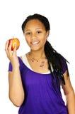 Girl holding apple. Isolated portrait of black teenage girl holding apple Stock Photo