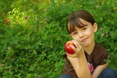 Girl holding an apple. Little girl sitting outside and holding an apple Royalty Free Stock Photo