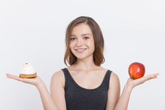 Girl holding apple and cupcake stock photography