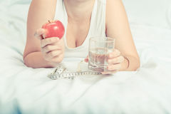 Girl  holding an Apple and a glass of water. Stock Photo