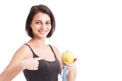 Girl holding apple and measuring tape. Young sport girl holding apple and measuring tape over white background Stock Photo