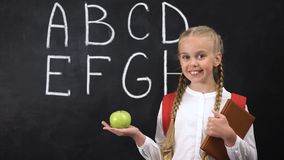 Girl holding apple near chalkboard, healthy snacking for kids, alphabet written. Stock footage stock footage