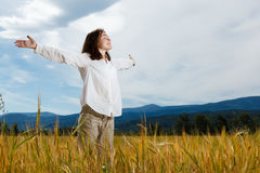 Girl holding arms up. Against blue sky Stock Photography