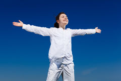 Girl holding arms up. Against blue sky Royalty Free Stock Image