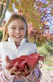 Girl (7-9) holding autumn leaves in park, smiling, close-up, portrait Royalty Free Stock Photos