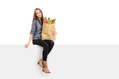 Girl holding bag of groceries seated on billboard Stock Image