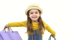 Girl holding bags in front of him, raises to the side and smiling. Slow motion stock footage