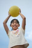 Girl holding ball. Happy girl holding yellow ball Royalty Free Stock Image