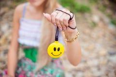 Girl holding a ball with smiling face. Girl holding a yellow ball with a smiling face royalty free stock photos