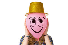 Girl holding balloon with smiling face and hat Royalty Free Stock Photography