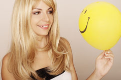 Girl holding a balloon. Young woman holding smiley face balloon Royalty Free Stock Image