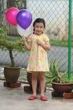 Girl holding balloons stock image