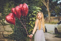 Girl holding balloons Stock Images