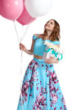 Girl holding balloons, box with flowers and smiling Stock Images