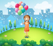 A girl holding balloons in the city Stock Photography