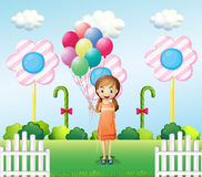 A girl holding balloons in the garden Stock Image