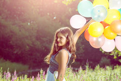 Girl holding balloons in hand Stock Photography
