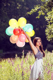 Girl holding balloons in hand Stock Photos