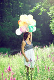 Girl holding balloons in hand Royalty Free Stock Image