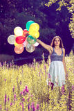 Girl holding balloons in hand Stock Images