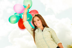 Girl holding balloons sky background Royalty Free Stock Photography