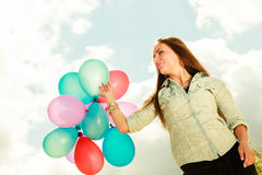 Girl holding balloons sky background Stock Photo