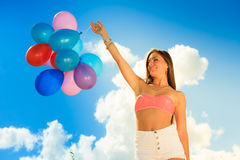 Girl holding balloons sky background Royalty Free Stock Image